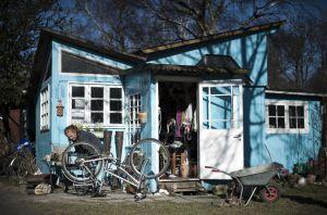 Una mujer repara su bicicleta en la entrada de su casa. J.NACKSTRAND