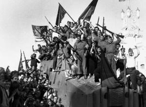 La milicia anarquista de la Confederación Nacional del Trabajo agita sus banderas y rifles para la cámara en Barcelona durante la Guerra Civil Española. California. 1937 Barcelona, España