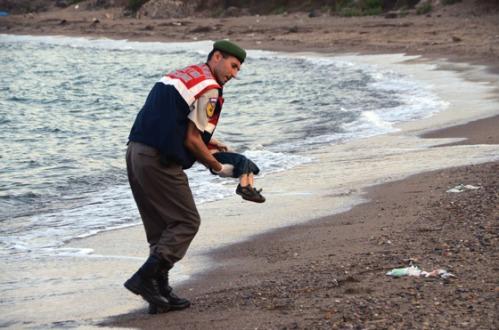 Un policia traslada el cadaver de un nino en una playa de turquia. El niño de tres años y su hermano, también muerto en el naufragio, procedían de Kobani, símbolo de la resistencia kurda