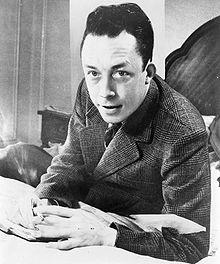 220px-Albert_Camus,_gagnant_de_prix_Nobel,_portrait_en_buste,_posé_au_bureau,_faisant_face_à_gauche,_cigarette_de_tabagisme