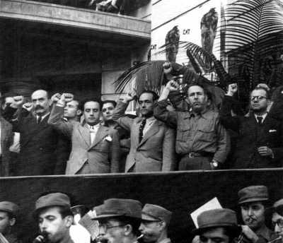 """Joan García Oliver, con Aurelio Fernández y Ricardo Sanz, puño en alto, en el acto de inauguración de la Vía Durruti (antigua Via Laietana) el 1 de julio de 1937, tras los « Hechos de Mayo """" de ese año [Fotografía de Pérez de Rosas]"""